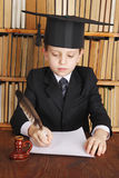 Professor. Child as a professor with quill and paper in library stock photos