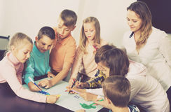 Professor and children drawing. Professor and collective of elementary age children drawing together one picture Royalty Free Stock Photography
