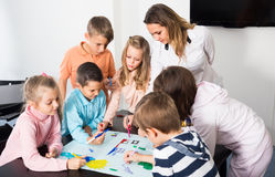 Professor and children drawing. Professor and elementary age children drawing together one picture indoors Royalty Free Stock Images
