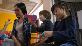 Professor com as crianças diversas que criam brinquedos na lição video estoque