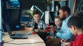 Professor com as crianças que exploram a impressão 3d