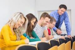 Professor com as estudantes universitário na sala de aula fotografia de stock