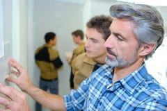 Professor com estudantes do ofício imagem de stock royalty free