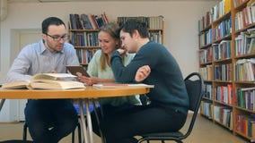 Professor com grupo de estudantes que trabalham na tabuleta digital na biblioteca Fotos de Stock Royalty Free