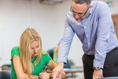 Professor com o estudante na sala de aula Imagens de Stock Royalty Free