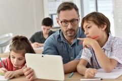 Professor com os estudantes na classe que usa a tabuleta Foto de Stock Royalty Free