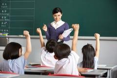 Professor com os estudantes na sala de aula chinesa da escola fotografia de stock