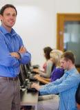 Professor com os estudantes que usam computadores na sala de computador Fotos de Stock