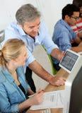Professor com os estudantes que usam a tabuleta na classe imagem de stock royalty free