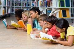 Professor com os livros de leitura dos estudantes ao encontrar-se para baixo fotos de stock royalty free