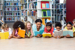 Professor com os livros de leitura dos estudantes ao encontrar-se para baixo imagens de stock royalty free