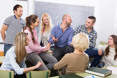 Professor consulting different age students Royalty Free Stock Images