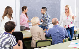 Professor consulting different age students Stock Images