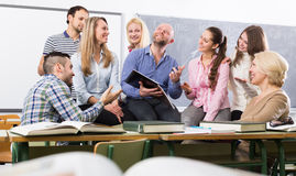 Professor consulting different age students. Professor consulting a different age students at a extension courses in classroom Stock Photo