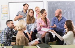 Professor consulting different age students Stock Photos