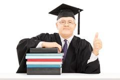Professor da faculdade assentado na tabela com os livros que gesticulam a felicidade imagens de stock