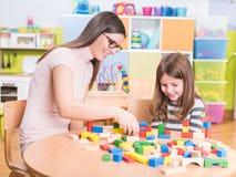 Professor de jardim de infância e jogo de sorriso bonito da menina Fotografia de Stock Royalty Free