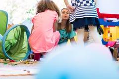 Professor de jardim de infância dedicado que coordena uma atividade do divertimento para crianças foto de stock royalty free