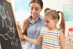 Professor de jardim de infância e criança pequena perto do quadro Aprendizagem e jogo fotos de stock