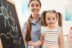 Professor de jardim de infância e criança pequena perto do quadro Aprendizagem e jogo foto de stock royalty free