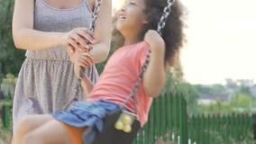 Professor de jardim de infância que balança a menina afro-americano pequena feliz, puericultura vídeos de arquivo