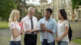 Professor, der der Gruppe multiethnischen Studenten Aufgaben, Bildung gibt stockfotografie