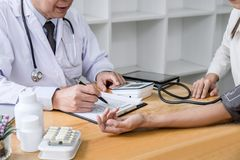 Professor doctor attentive patient being measuring and checking blood pressure to patient, hospital and medicine concept.  stock images