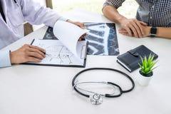 Professor Doctor, das Gespräch mit Patienten hat und Röntgenfilm bei der Diskussion hält, Symptome oder Ratschlagdiagnose erkläre stockbilder