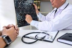 Professor Doctor, das Gespräch mit Patienten hat und Röntgenfilm bei der Diskussion hält, Symptome oder Ratschlagdiagnose erkläre lizenzfreie stockbilder