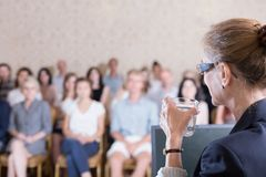 Professor drinking water. Image of professor drinking water during her presentation royalty free stock photo
