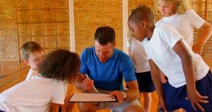 Professor e alunos dos esportes que discutem sobre a prancheta no campo de básquete 4k filme