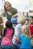 Professor e crianças de jardim de infância que olham o globo