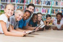 Professor e crianças que encontram-se no assoalho usando a tabuleta digital na biblioteca fotos de stock royalty free
