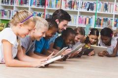 Professor e crianças que encontram-se no assoalho usando a tabuleta digital na biblioteca Fotografia de Stock Royalty Free