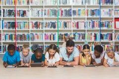 Professor e crianças que encontram-se no assoalho usando a tabuleta digital na biblioteca foto de stock royalty free