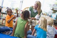 Professor e crianças que olham o seedling Imagem de Stock