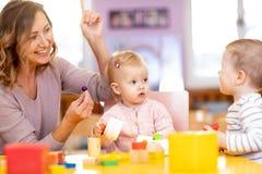 Professor e crianças que têm o divertimento na aprendizagem no jardim de infância Professor, educação, crianças e conceito da esc foto de stock