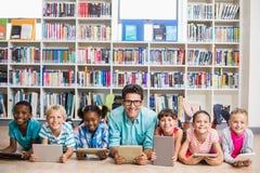 Professor e crianças que usam a tabuleta digital na biblioteca foto de stock