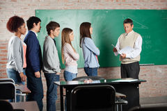 Professor With Exam Results While Students. Mature male professor with exam results while students standing in a row at classroom desk royalty free stock images