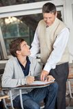 Professor Explaining Exam To Student In Classroom Stock Photography