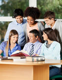 Professor Explaining Students At Desk In Classroom Stock Images