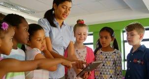 Professor fêmea asiático que ensina na tabuleta digital na biblioteca escolar 4k filme
