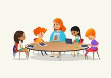 Professor fêmea do ruivo que mostra a imagem às crianças que sentam-se em torno da mesa redonda na classe com o PC do portátil e  Fotografia de Stock Royalty Free