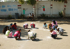 Professor fêmea no lenço principal na escola que recolhe as meninas no círculo e que tira na areia Fotos de Stock Royalty Free