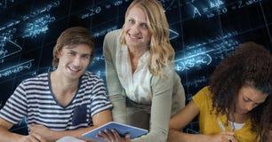 Professor fêmea que mantém o PC da tabuleta por estudantes contra equações da matemática fotografia de stock