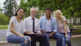 Professor feliz e estudantes multi-étnicos que sentam-se no banco, sorrindo na câmera vídeos de arquivo