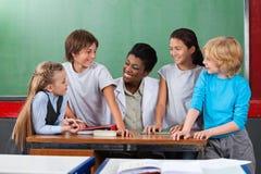 Professor feliz With Students Communicating na mesa fotografia de stock