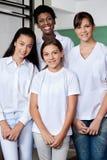 Professor With Female Students que está junto dentro Imagem de Stock