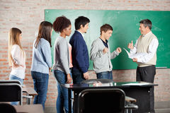 Professor Gesturing Thumbsup To Student In. Professor gesturing thumbsup to successful male student with classmates standing in a row at classroom Royalty Free Stock Image