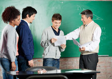 Professor Giving Exam Result To Student At. Happy male professor giving exam result to student with classmates standing in a row at classroom Stock Photos